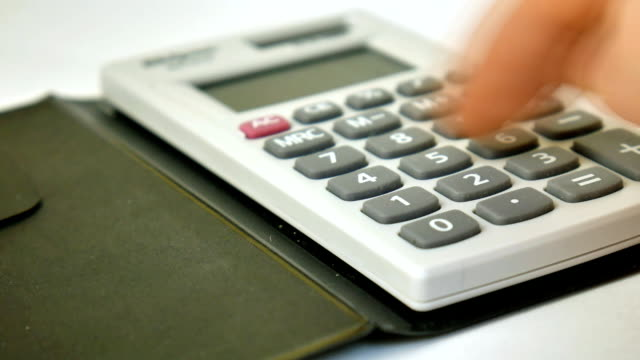 Counting on calculator. Macro. Finger presses the button calculator. Closeup. video