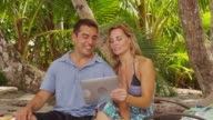 Couple at beach using digital tablet. video