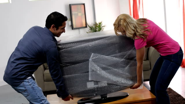 Couple at home setting up new TV video