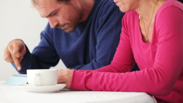 Couple at home using digital tablet video