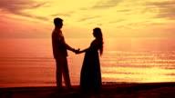 Couple beach sunset. Couple silhouette beach. Pregnant couple sunset video