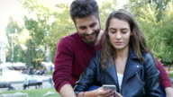 Couple browsing on a mobile phone and talking video