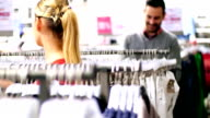 Couple buying clothes at retail store. video