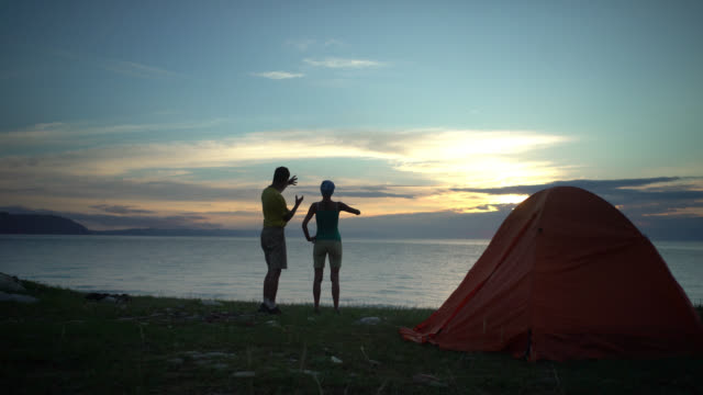 Couple camping looking at sunrise in the morning video