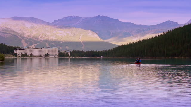 Couple Canoe Across Mountain Lake In Evening video