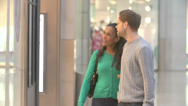 Couple Carrying Bags And Looking In Mall Shop Windows video