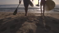 Couple carrying their paddle boards down to the water video