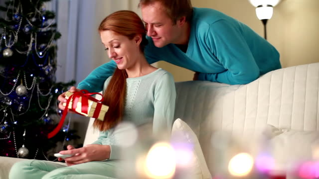 Couple celebrate Christmas. The man gives a gift a young charming woman. video