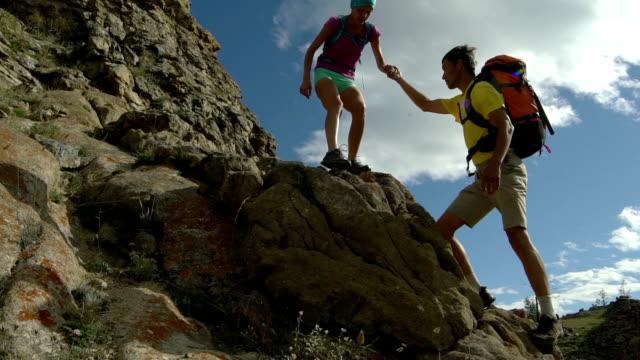 Couple climbing mountain range video
