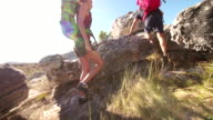 Couple climbing rock while hiking on summer day in nature video