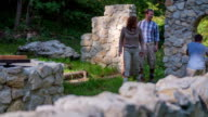 Couple coming in the castle ruins tu start treasure hunt video