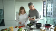 Couple cooking at home following an online recipe video