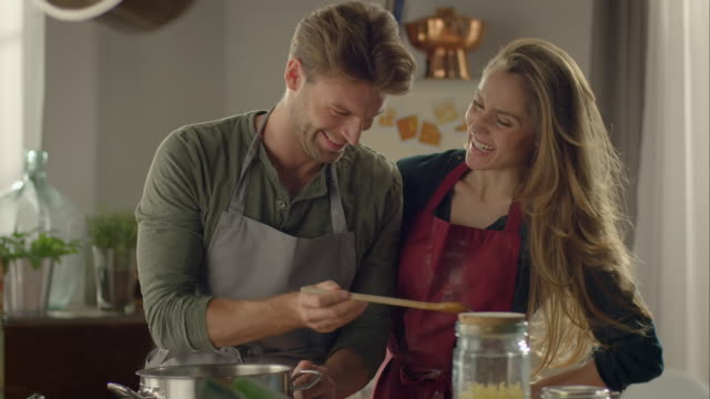 Couple cooking together in kitchen and tasting food video