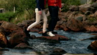 Couple crossing a stream together in the countryside video