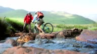 Couple crossing a stream together with their bikes video