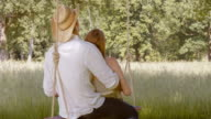 SLO MO Couple cuddling on a swing in meadow video