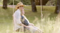 SLO MO DS Couple cuddling on a swing in nature video