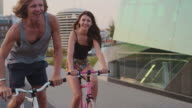Couple cycling along urban street together video