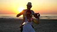 Couple dancing with a firework candle at the beach at sunrise video