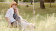 SLO MO DS Couple daydreaming on a swing in nature video