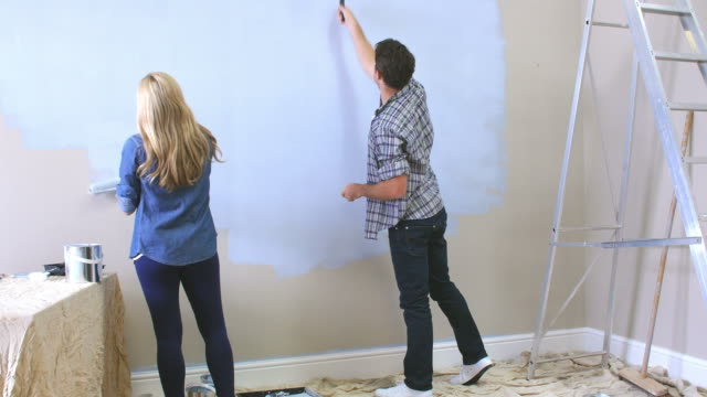 Couple Decorating Room Using Paint Rollers On Wall video