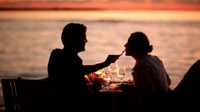 couple dining on beach at sunset video