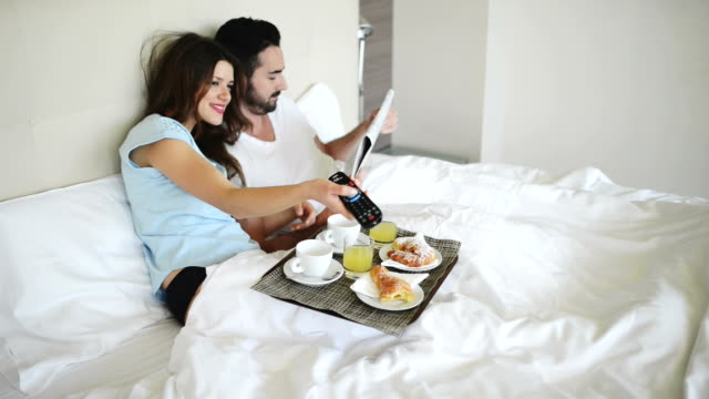 couple doing breakfast on the bed of hotel room video