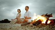PAN Couple doing half lotus on beach by the fire video