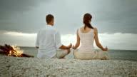 PAN Couple doing yoga on the beach video