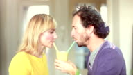 Couple drinking smoothie from same drinking glass video