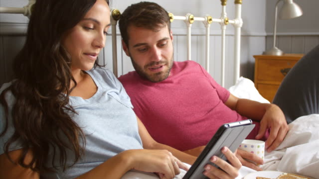 Couple Eating Breakfast In Bed Whilst Using Digital Tablet video