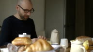 Couple eating breakfast in sunny kitchen video