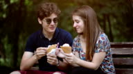 Couple eating ice cream in park video