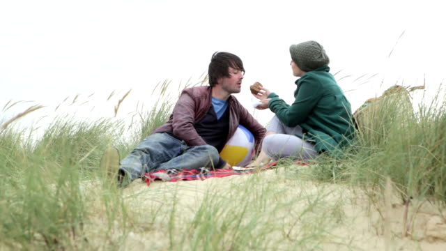 Couple eating on sand dune video