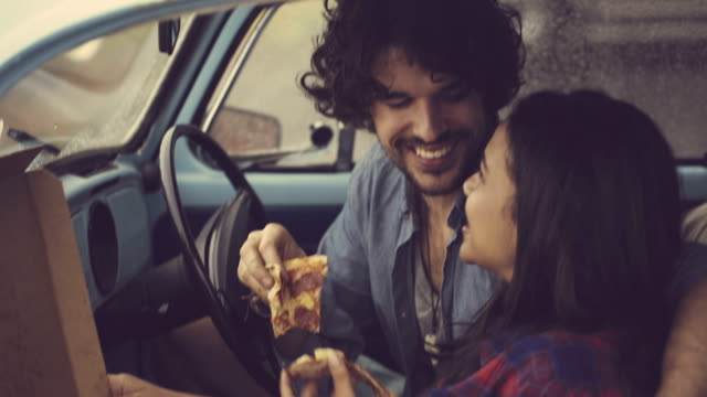 Couple eating pizza in retro car video