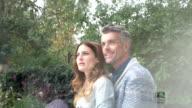 Couple embrace and gaze upwards -  through glass window video