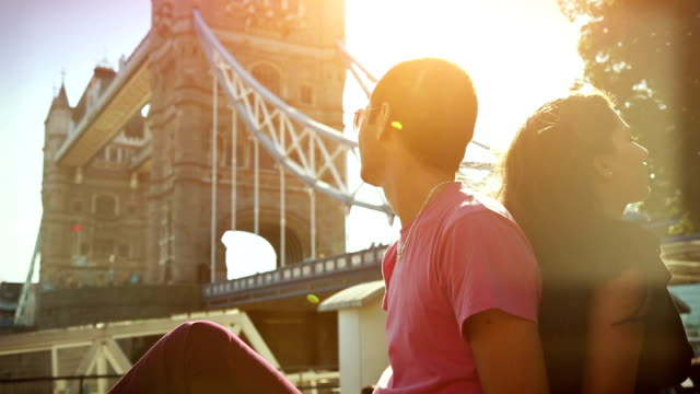 Couple enjoy sun in front of the Tower Bridge video