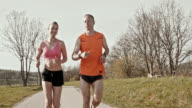SLO MO TS Couple enjoying their jog on in sunshine video