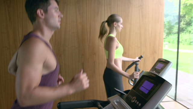 Couple exercising on treadmill and cross trainer together video