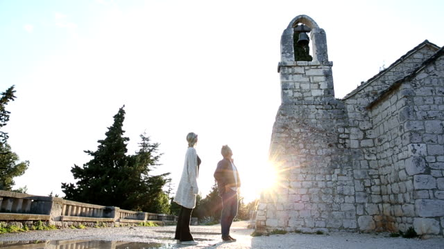 Couple explore ancient chapel on Mediterranean hillside video