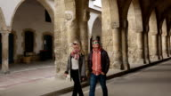 Couple explore portico of ancient cathedral video