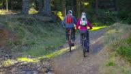 SLO MO Couple going uphill on mountain bikes video