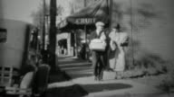 1936: Couple grocery shopping from fruit store walking bags of food. video