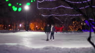 Couple has skating date on a snowy winter evening. video