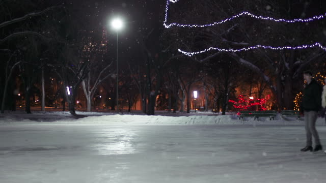 Couple has skating date on a snowy winter night. video