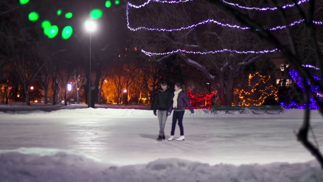 Couple has skating date on a winter evening. video
