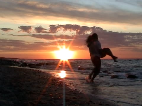 Couple having fun at the beach during sunset video