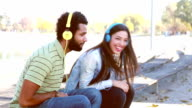 Couple having fun listening to music on headphones at the park video