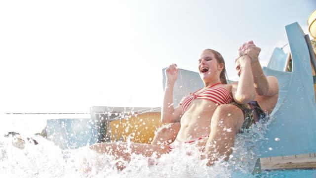 SLO MO Couple having fun on a water slide video