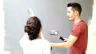 Couple having fun while painting wall in new home video